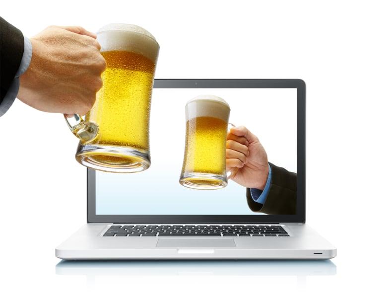Manos brindando con cerveza desde el ordenador